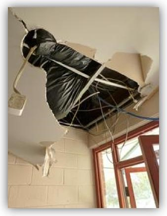 Figure 1: shows damaged ceiling with plasterboard pulled down and wiring exposed