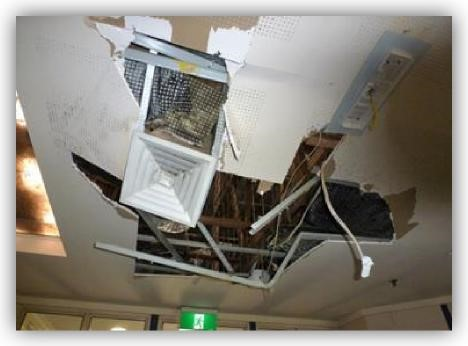 Digure 2: Damaged ceiling with air-conditioning vent pulled free, plasterboard ripped and wiring exposed