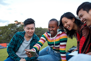 Four laughing young people sit in a park and look at a phone.