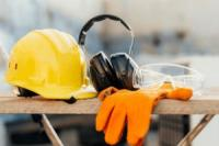 Yellow hard hat, ear protectors and orange work gloves rest on a wooden bench