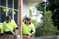 Alt text: Two young tradespeople wearing high vis clothing working on a construction job