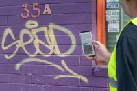 Man in hi-vis vest photographing graffiti on a purple wall.